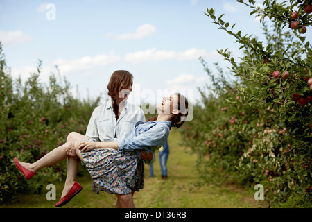Rows of fruit trees in an organic orchard Two young women laughing one carrying the other - Stock Photo