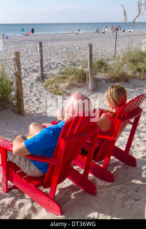 Florida Sanibel Captiva Island Gulf of Mexico beach water sand Adirondack chairs red man woman couple relaxing The - Stock Photo