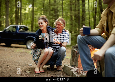 Three people sitting around a campfire at dusk - Stock Photo