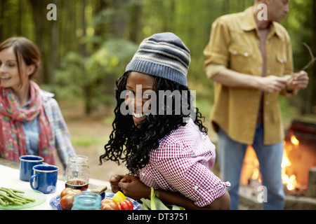 A campsite clearing in the woods People seated - Stock Photo