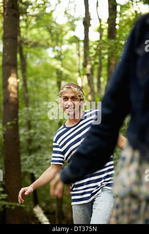 Two people walking along a fallen tree trunk - Stock Photo