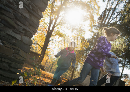 Three children in the autumn sunshine. Playing outdoors throwing the fallen leaves  in the air. - Stock Photo