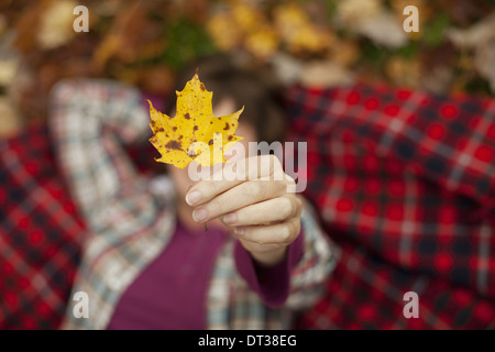 A woman lying on a red tartan picnic blanket, looking upwards, holding a maple leaf. - Stock Photo