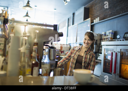 A person, barista, behind the counter at a coffee shop. A coffee machine cappuccino on the counter. - Stock Photo