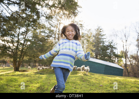 A young girl in a  blue stripy top running in a field of sheep at an animal sanctuary. - Stock Photo