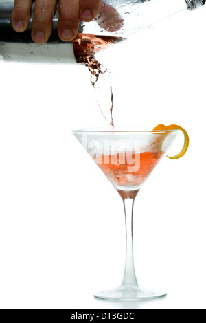 male hands pouring a vodka cocktail in to a chilled martini glass with a lemon garnish - Stock Photo