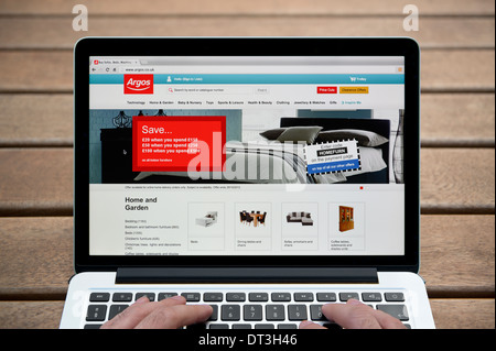 The Argos website on a MacBook against a wooden bench outdoor background including a man's fingers (Editorial use - Stock Photo