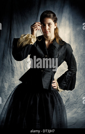 A young woman wears vintage Victorian/Edwardian clothing as she strikes a pose in a studio setting. - Stock Photo