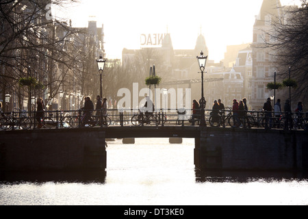 Silhouette of people and bicycles riding over a bridge over a canal in Amsterdam, Holland - Stock Photo