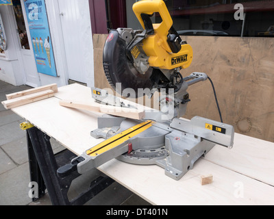 Shop fitter's workbench on the pavement with a woodworking electric power saw on a mitre cutting stand - Stock Photo