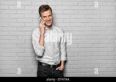 Male portrait smiling Mobile Phone studio brick looking camera