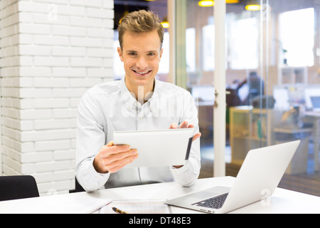 Man business tablet pc desk laptop message e-mail looking camera - Stock Photo