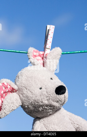 Soft toy mouse hanging on the washing line, against a blue sky background. - Stock Photo