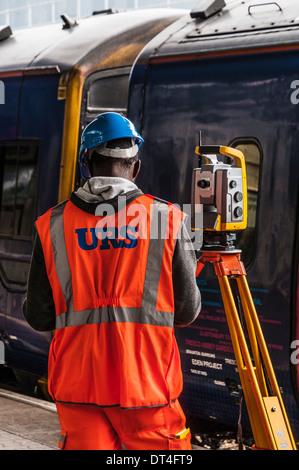 Surveyor standing next to his measuring equipment on a railway station platform with train in the background - Stock Photo