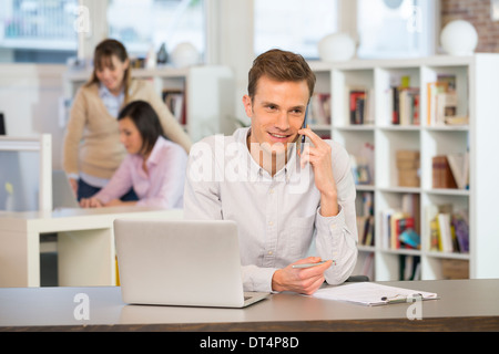 Cheerful man on the phone at the office - Stock Photo