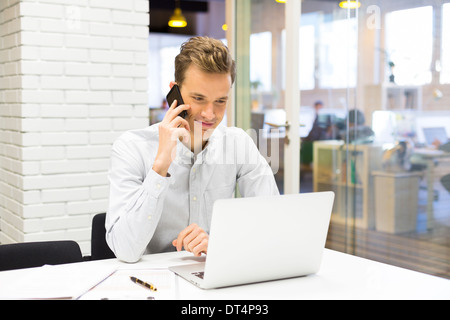 Businessman calling with mobile phone in office - Stock Photo