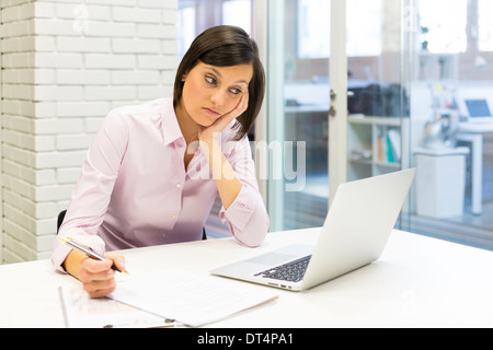 Tired businesswoman at desk working with computer and paper - Stock Photo
