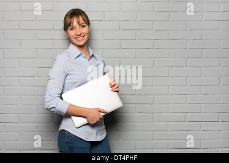 Portrait of young woman with computer in studio, looking camera - Stock Photo