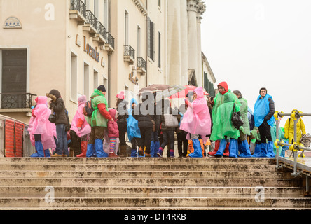 Venice, Italy. Tourists and children in wet weather clothing and rain boots, standing on a bridge during rain. - Stock Photo