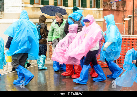 Venice, Italy. People in wet weather clothing, rain ponchos, and rain boots, standing on bridge during rain. - Stock Photo