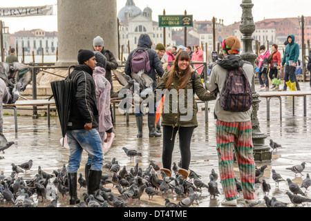 Venice, St Mark´s Square, Italy. Young woman gets photographed with a smartphone while pigeons sitting on her arms. - Stock Photo