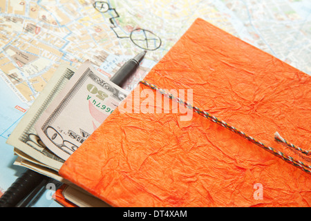 Close-up Travel Arrangement of Dollars, Map and notepad diary - Stock Photo