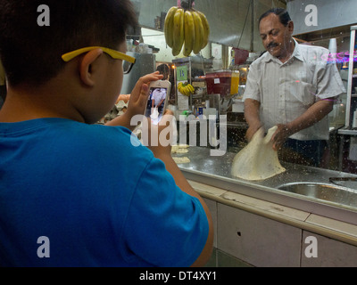 Boy taking video on iPhone of baker making naan at muslim restaurant in Singapore - Stock Photo