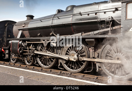A steam train increasing steam ready to depart from a station - Stock Photo