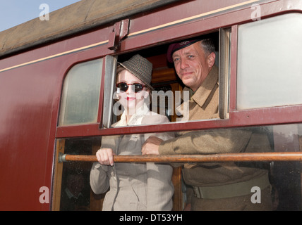 Two people looking out of a train window in 1940's costume - Stock Photo