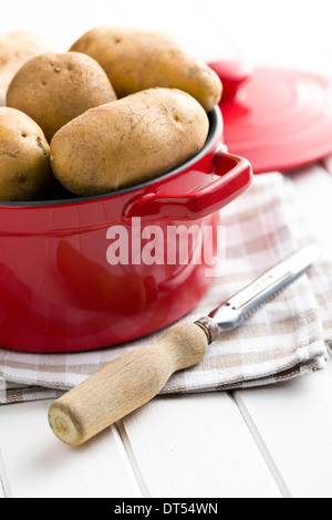 the uncooked potatoes and old wooden peeler - Stock Photo