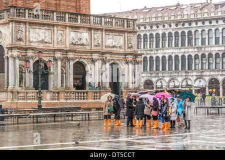 Venice, Italy. Asian tourists in wet weather clothing, umbrellas, and orange rain boots on St Mark´s Square, Campanile - Stock Photo