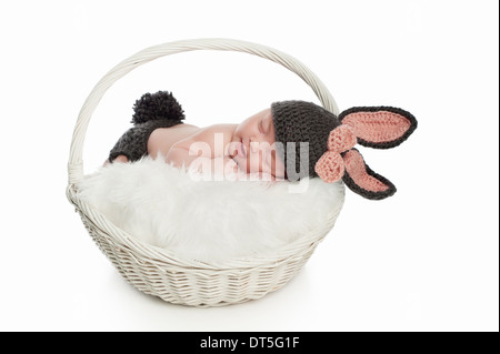 Smiling baby girl sleeping in a basket and wearing a bunny costume. - Stock Photo