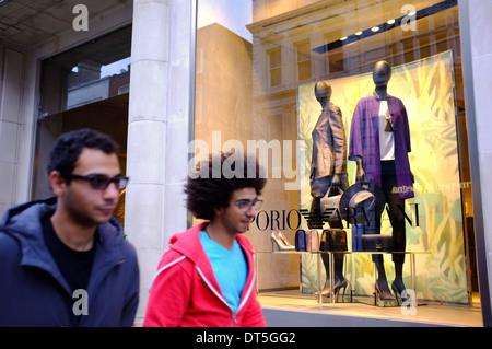 Two young affluent ethnic men walking past Emporio Armani designer fashion boutique on Bond street, London - Stock Photo