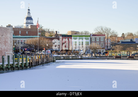 The Annapolis State House seen behind frozen dock front in winter - Stock Photo