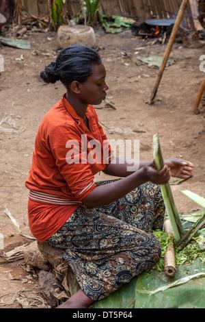 A Dorze Woman Prepares Kocho (Unleavened Bread) Made from The False Banana Tree, Hayzo Village, Arba Minch, Ethiopia - Stock Photo