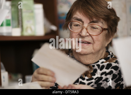 Elderly woman reading a letter - Stock Photo