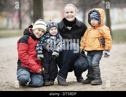 Happy mother with her three young children - Stock Photo
