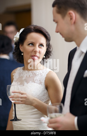 Bride and groom enjoy a drink at the wedding - Stock Photo