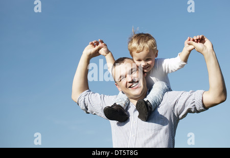 Dad giving his young son a piggy back ride - Stock Photo