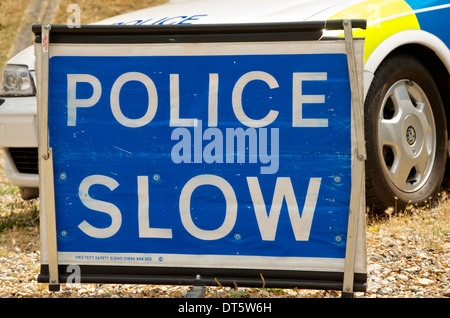 Police Slow sign in front of a police car - Stock Photo