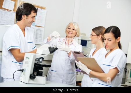 Scientists Discussing Over Blood Sample In Laboratory - Stock Photo