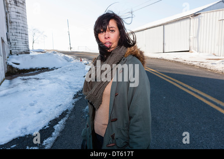 Young woman standing outside farm buildings in winter - Stock Photo