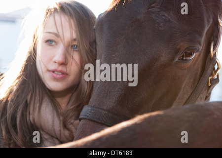 Close up of young woman with horses - Stock Photo