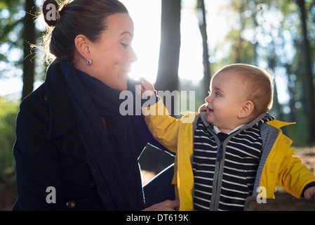 Mother and young toddler in woodland park - Stock Photo