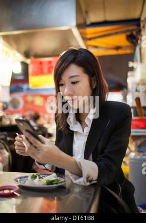 Businesswoman using cellular phone, night market, Taipei, Taiwan - Stock Photo