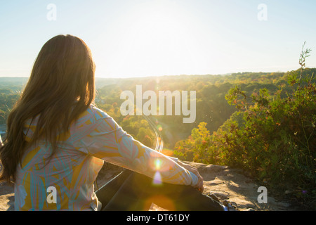 Mid adult woman sitting on elevated rock watching sunrise - Stock Photo