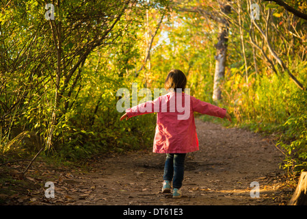 Happy female toddler strolling through autumn woodland - Stock Photo
