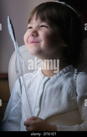 Happy female toddler with wand, dressed up in fairy wings - Stock Photo