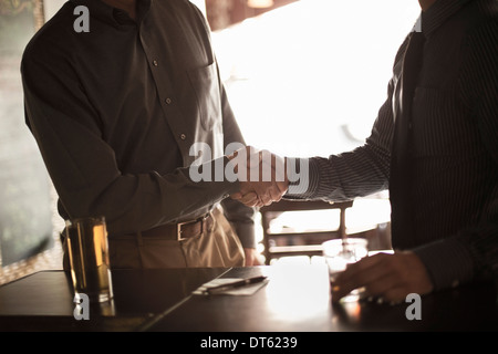 Two businessmen shaking hands in wine bar - Stock Photo