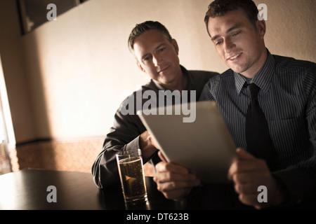 Two business colleagues looking at digital tablet in wine bar - Stock Photo